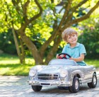 30993029 - little boy driving big toy car and having fun, outdoors.