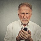 43388573 - closeup worried elderly man looking at his smart phone isolated on gray wall background
