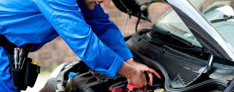 Smiling mechanic doing a maintenance check