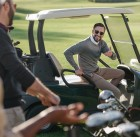 stylish golf player talking to his friends while sitting in golf cart on golf course