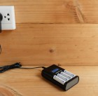 110308033 - battery charger with battery size aa rechargeable with charger plug in power outlet adapter on wooden table