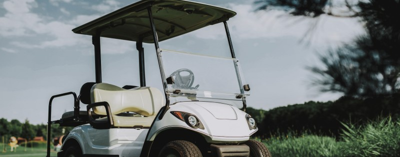 White Little Cart on Golf Field in Sunny Day. Healthy Lifestyle Concept. Golf Club. Sports in Summer. Vehicle on Field. Family Holiday. Outdoor Fun in Summer. Sunny Day. Electric Car.