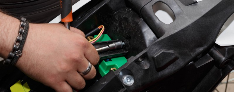 The wizard installs a new battery on the motorcycle after refueling and checking. Motorcycle repair and maintenance