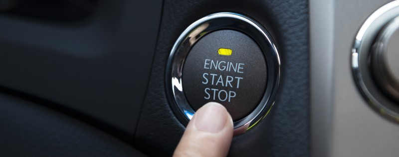 15729140 - finger pressing the engine start stop button of a car