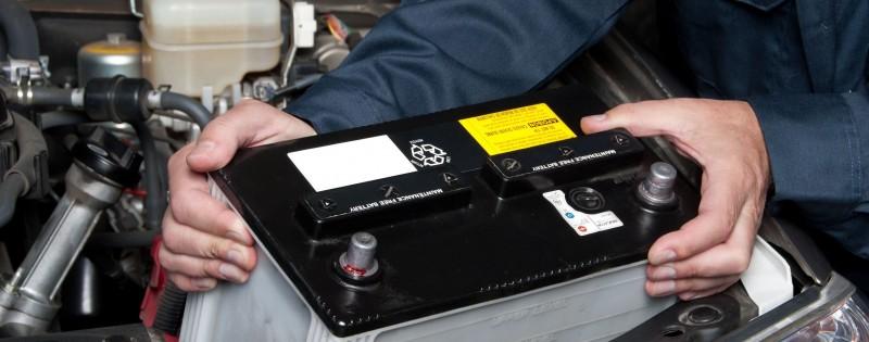 7909492 - a car mechanic replaces a battery.